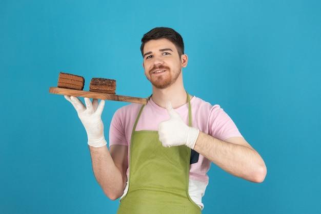 新鮮なケーキのスライスを保持し、親指を立てて身振りで示す若いハンサムな男。