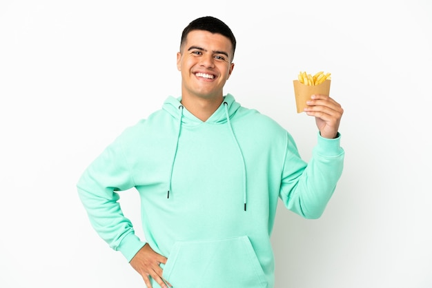 Young handsome man holding fried chips over isolated white background posing with arms at hip and smiling