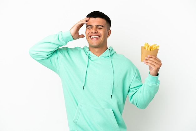 Young handsome man holding fried chips over isolated white background smiling a lot