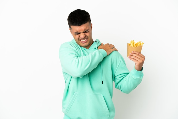 Young handsome man holding fried chips over isolated white background suffering from pain in shoulder for having made an effort