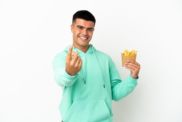 Молодой красавец держит жареные чипсы на изолированном белом фоне, делая приближающийся жест