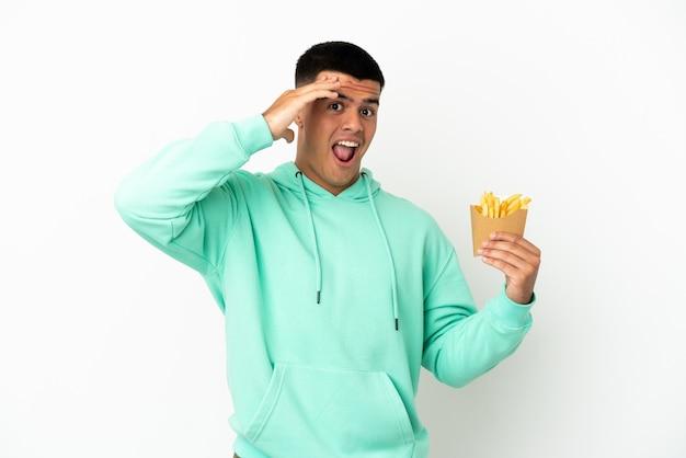 Молодой красавец держит жареные чипсы на изолированном белом фоне, делая неожиданный жест, глядя в сторону