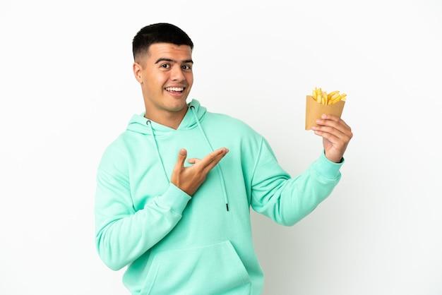 Молодой красавец держит жареные чипсы на изолированном белом фоне, протягивая руки в сторону, приглашая приехать