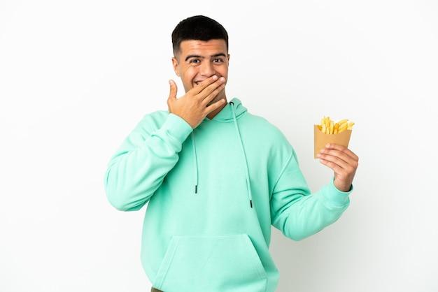 Молодой красавец, держащий жареные чипсы на изолированном белом фоне, счастливый и улыбающийся, прикрывая рот рукой