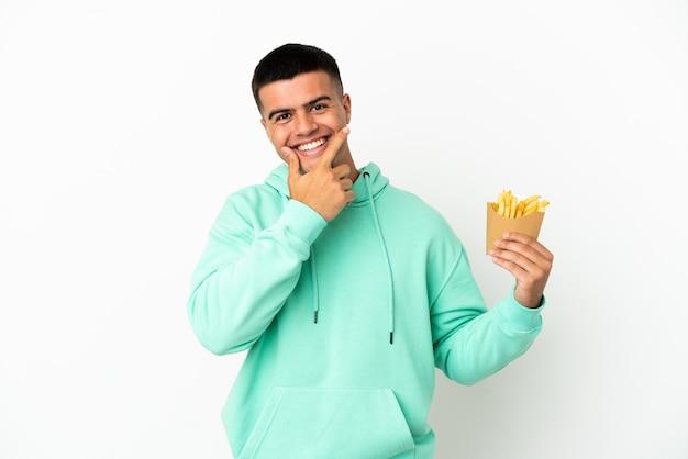 Молодой красавец, держащий жареные чипсы на изолированном белом фоне, счастлив и улыбается