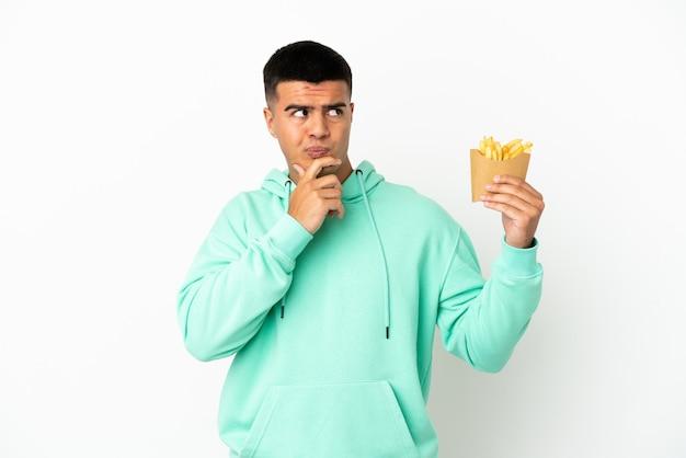 Молодой красавец держит жареные чипсы на изолированном белом фоне, сомневаясь и думая