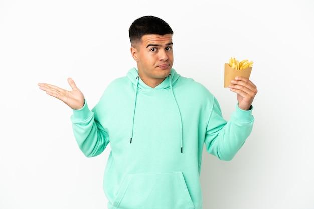 Молодой красавец держит жареные чипсы на изолированном белом фоне, сомневаясь, поднимая руки