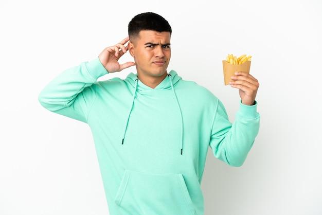 Молодой красавец держит жареные чипсы на изолированном белом фоне, сомневаясь