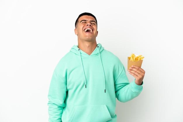 Молодой красавец, держащий жареные чипсы на изолированном белом фоне, смеясь