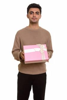 バレンタインの日の準備ができてギフトボックスを保持している若いハンサムな男