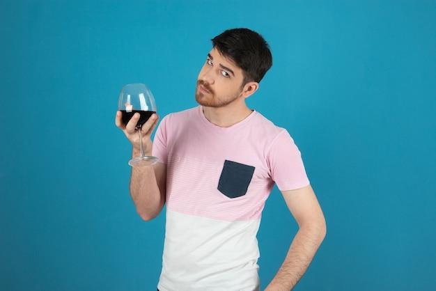 Giovane uomo bello che tiene in mano un bicchiere di vino e guarda la telecamera.