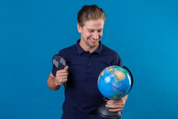 Молодой красивый мужчина держит глобус и увеличительное стекло, глядя на глобус, улыбаясь со счастливым лицом, стоящим на синем фоне
