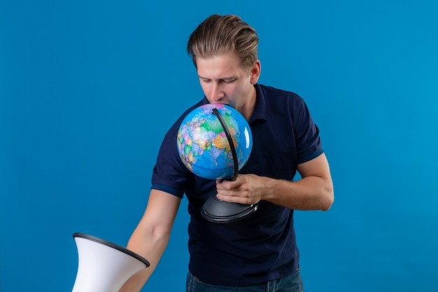 Giovane uomo bello che tiene globo e megafono cercando in piedi giocoso e felice su sfondo blu