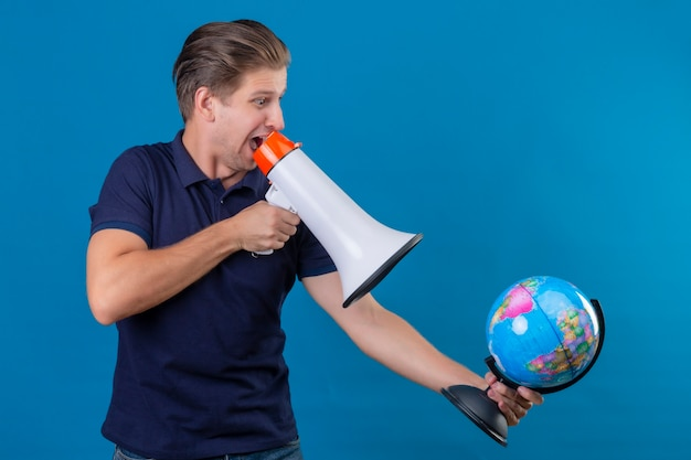 Young handsome man holding globe speaking to megaphone surprised and exited standing over blue background