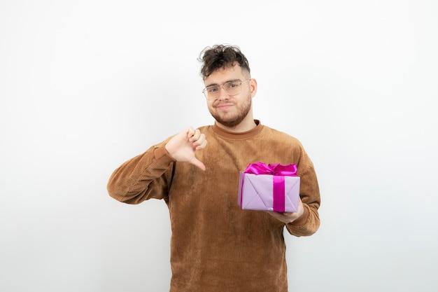 Giovane uomo bello che tiene il suo regalo di festa e che mostra i pollici verso il basso.