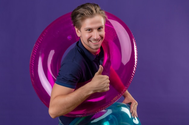 Young handsome man holding inflatable ring looking at camera with happy face smiling cheerfully showing thumbs up standing over purple background