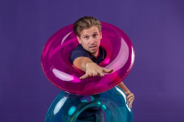 Young handsome man holding inflatable rings stretching out hands looking at camera asking for help standing over purple background