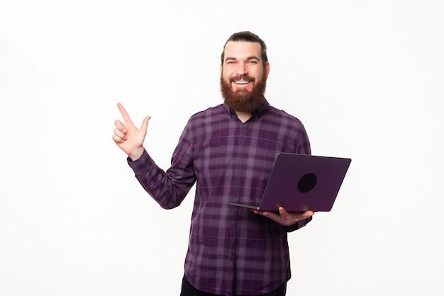 Молодой красивый мужчина держит ноутбук и указывая в сторону