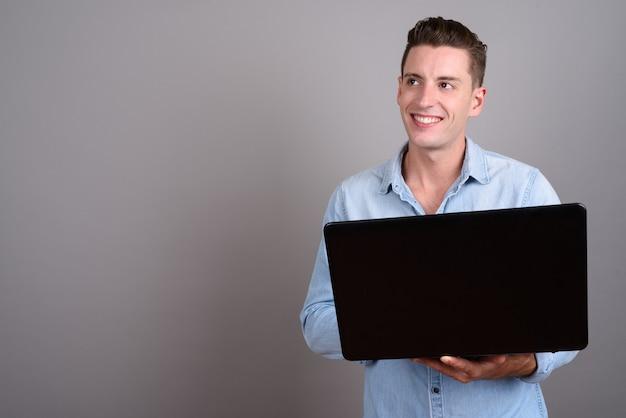 灰色のラップトップを保持している若いハンサムな男