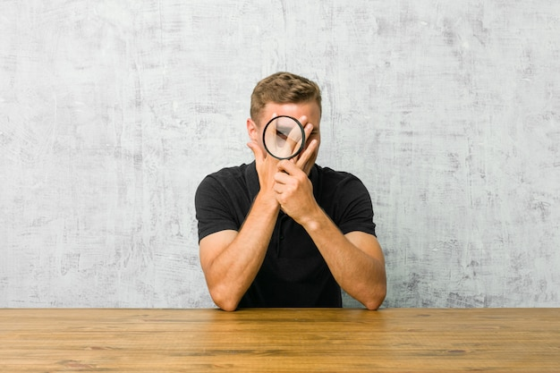 Young handsome man holding a magnifying glass blink through fingers frightened and nervous.