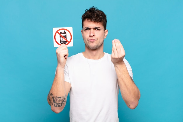 Young handsome man holding mobile phone use prohibited signboard