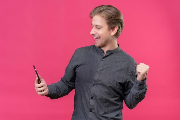 Giovane uomo bello che tiene il telefono cellulare