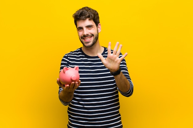 Young handsome man holding a piggy bank against orange backgroun