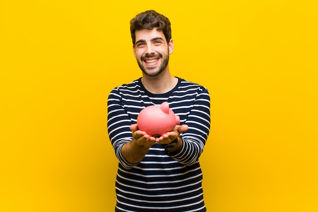 Young handsome man holding a piggy bank on orange