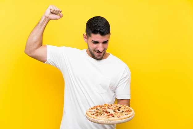 Young handsome man holding a pizza over isolated yellow wall celebrating a victory
