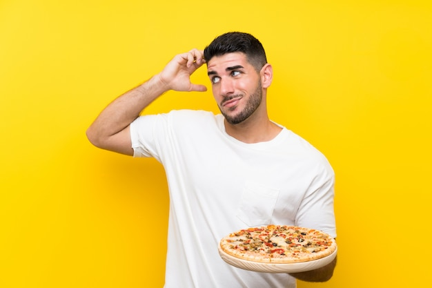 Young handsome man holding a pizza over isolated yellow wall having doubts and with confuse face expression