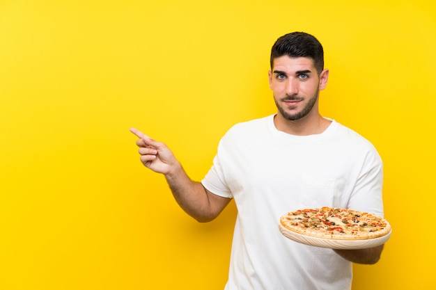Young handsome man holding a pizza over isolated yellow wall pointing to the side to present a product