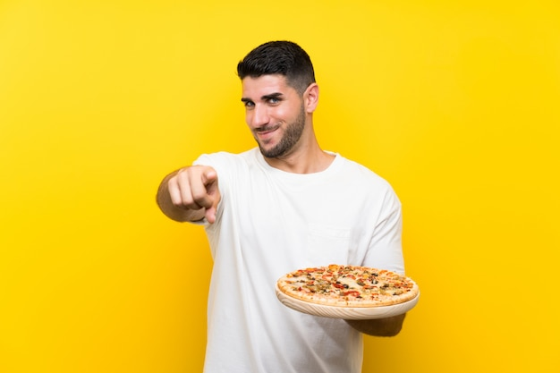 Young handsome man holding a pizza over isolated yellow wall points finger at you with a confident expression