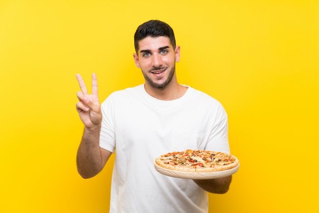 Young handsome man holding a pizza over isolated yellow wall smiling and showing victory sign