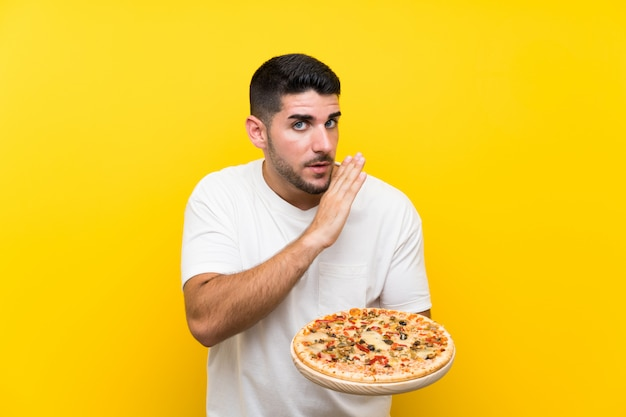 Young handsome man holding a pizza over isolated yellow wall whispering something