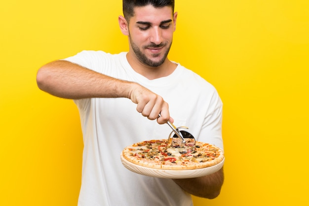 Young handsome man holding a pizza over isolated yellow wall