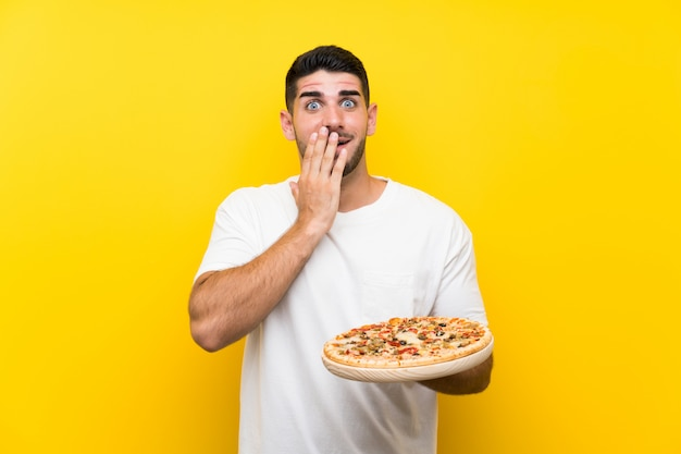 Young handsome man holding a pizza  on yellow wall with surprise facial expression