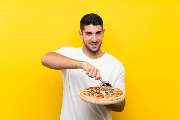 Young handsome man holding a pizza  on yellow wall