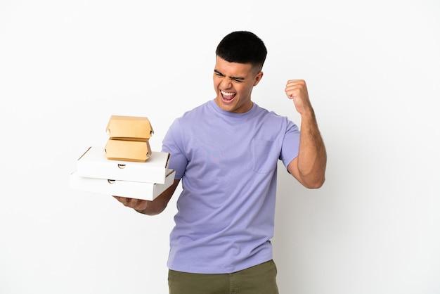 Молодой красавец, держащий пиццу и гамбургеры на изолированном белом фоне, празднует победу