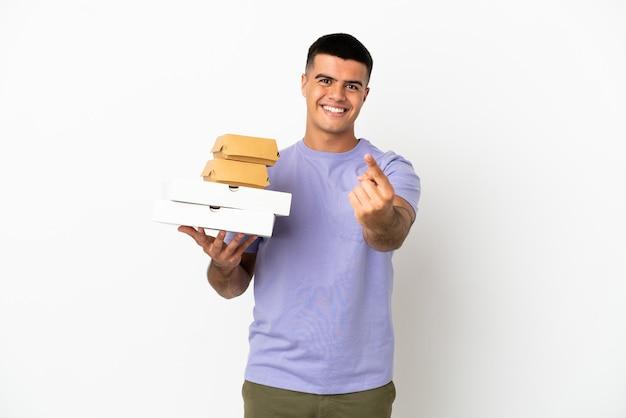 Молодой красавец держит пиццу и гамбургеры на изолированном белом фоне, делая приближающийся жест