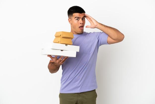 Молодой красавец, держащий пиццу и гамбургеры на изолированном белом фоне, делает неожиданный жест, глядя в сторону