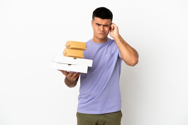 외진 흰색 배경 위에 피자와 햄버거를 들고 있는 잘생긴 청년은 좌절하고 귀를 막고 있다