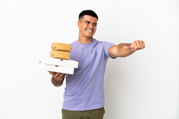 Молодой красавец держит пиццу и гамбургеры на изолированном белом фоне, показывая большой палец вверх