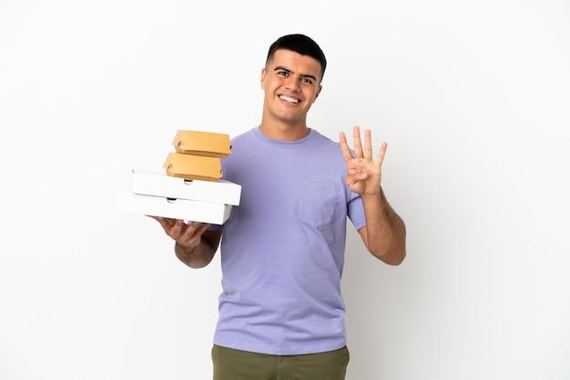 Молодой красавец, держащий пиццу и гамбургеры на изолированном белом фоне, счастлив и считает четыре пальцами