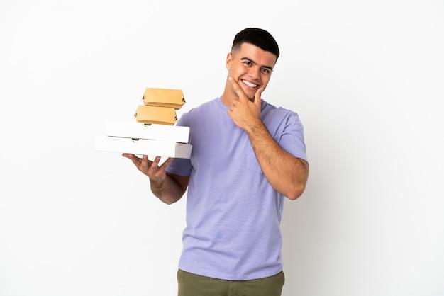Молодой красавец, держащий пиццу и гамбургеры на изолированном белом фоне, счастлив и улыбается