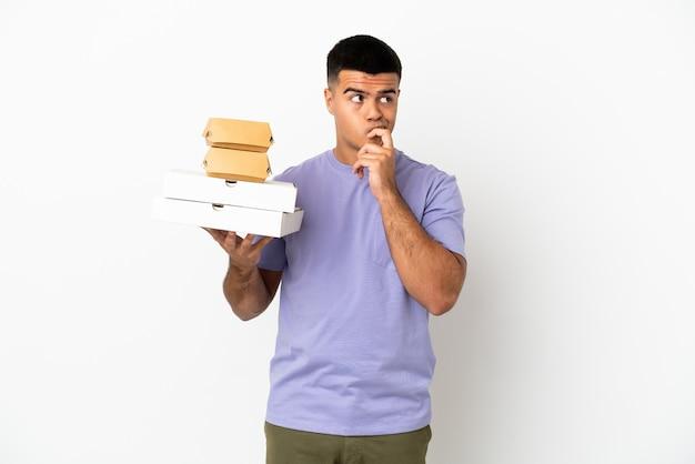 Молодой красавец, держащий пиццу и гамбургеры на изолированном белом фоне, сомневаясь и думая