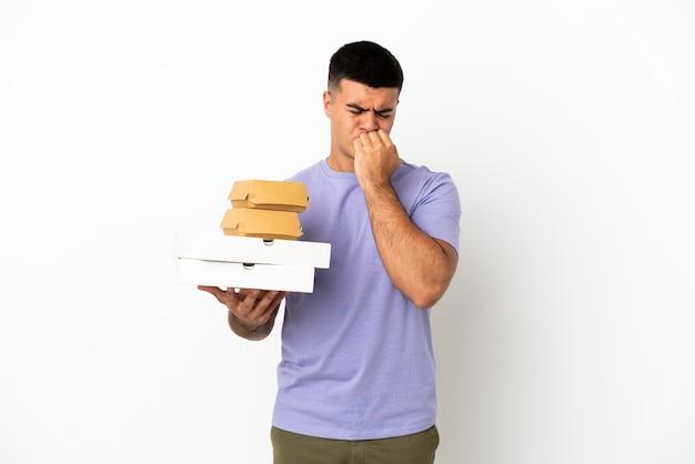 Молодой красавец, держащий пиццу и гамбургеры на изолированном белом фоне с сомнениями
