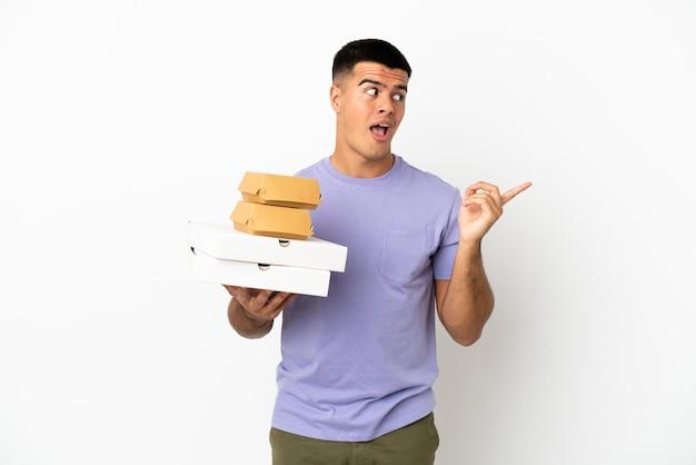Молодой красавец держит пиццу и гамбургеры на изолированном белом фоне, намереваясь понять решение, подняв палец вверх