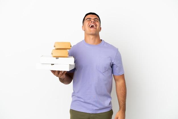 Молодой красавец, держащий пиццу и гамбургеры на изолированном белом фоне, смеясь