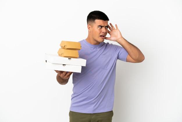 Молодой красавец держит пиццу и гамбургеры на изолированном белом фоне, слушая что-то, положив руку на ухо