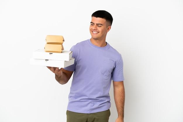 Молодой красивый мужчина держит пиццу и гамбургеры на изолированном белом фоне, глядя в сторону и улыбаясь